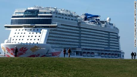 "Spectators look on as the ""Norwegian Joy"" cruise ship, previously named ""Norwegian Bliss"", makes its way over the river Ems near Emden, northern Germany, on March 27, 2017. The ship of the Norwegian Cruise Line, that was built at the Meyer Werft shipyard in Papenburg, northern Germany, is made ready to enter service. Final technical and nautical tests are due to be carried out during the following days on the North Sea. / AFP PHOTO / PATRIK STOLLARZ        (Photo credit should read PATRIK STOLLARZ/AFP/Getty Images)"