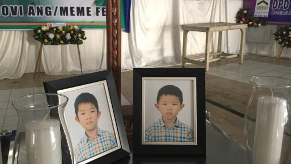 Photos of Vincensius Evan Hudojo and Nathanael Ethan Hudojo are displayed at a funeral home.