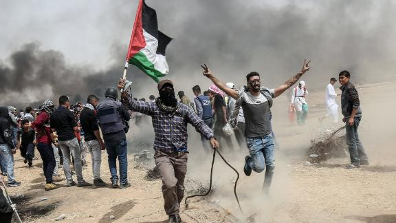 "TOPSHOT - Palestinian protesters pull a metal cable as they try to take down a section of barbed wire during clashes with Israeli forces on April 20, 2018, east of Khan Yunis, in the southern Gaza Strip during mass protests along the border of the Palestinian enclave, dubbed ""The Great March of Return,"" which has the backing of Gaza"