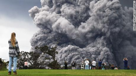 HAWAII VOLCANOES NATIONAL PARK, HI - MAY 15:  People watch at a golf course as an ash plume rises in the distance from the Kilauea volcano on Hawaii's Big Island on May 15, 2018 in Hawaii Volcanoes National Park, Hawaii. The U.S. Geological Survey said a recent lowering of the lava lake at the volcano's Halemaumau crater 'has raised the potential for explosive eruptions' at the volcano.  (Photo by Mario Tama/Getty Images)