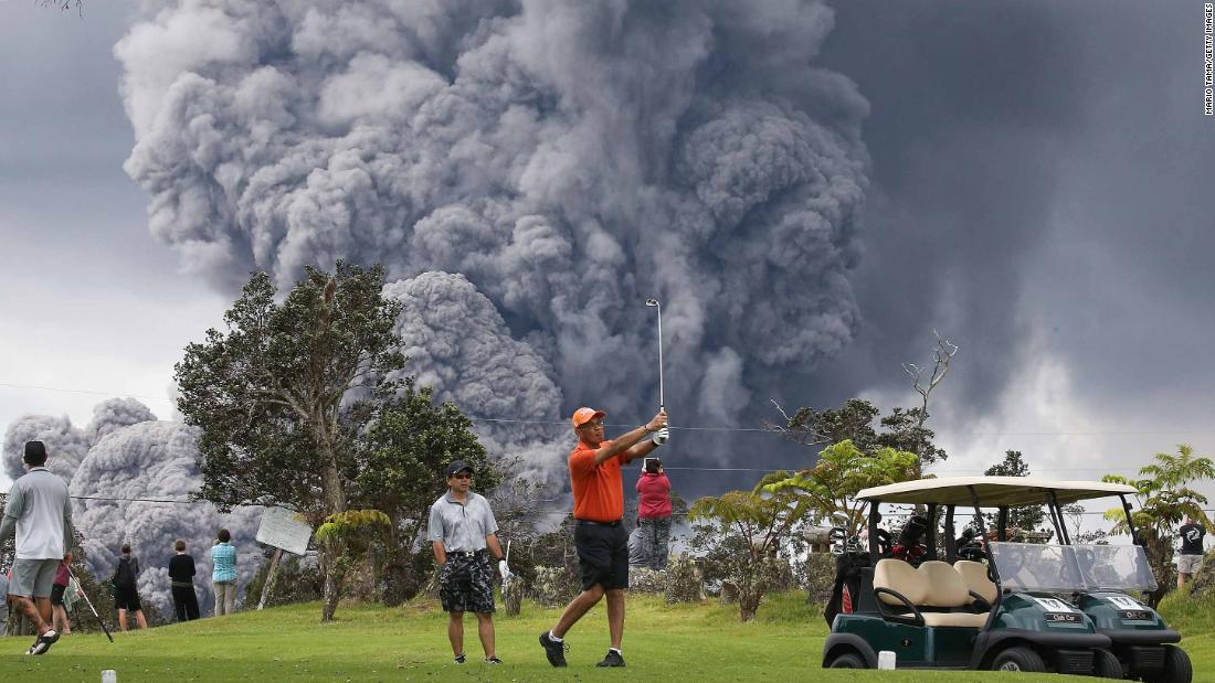 Stunning photos taken at Hawaii's Big Island on Tuesday show golfers coolly hitting the links even as a monstrous ash plume looms behind them from the Kilaueau volcano on May 15, 2018 at Hawaii Volcanoes National Park.