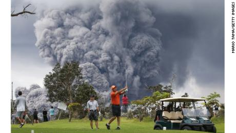 People play golf as an ash plume rises in the distance from the Kilauea volcano on Hawaii's Big Island on May 15, 2018 in Hawaii Volcanoes National Park, Hawaii.
