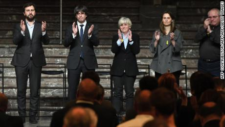 "(FromL) Former Health minister Antoni Comin, Catalonia's sacked leader Carles Puigdemont, former Councillor of Education of the Generalitat of Catalonia Clara Ponsati, former Catalan Minister of Agriculture, Livestock, Fisheries and Food Meritxell Serret and former Catalan Minister of Culture Lluis Puig Gordi applaud during a meeting with Catalan mayors in Brussels on November 7, 2017. Around 200 pro-independence Catalan mayors flew to Brussels on November 7 and held a protest demanding the release of their region's ""political prisoners"". Puigdemont claimed on November 7, 2017, that he fled to Belgium because Spain was preparing a ""wave of oppression and violence"" against his separatist movement.  / AFP PHOTO / Emmanuel DUNAND        (Photo credit should read EMMANUEL DUNAND/AFP/Getty Images)"