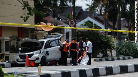 Indonesian policemen examine a car used by attackers outside the police headquarter in Pekanbaru, Riau following attacks on May 16, 2018. - Four men were shot and killed as they staged an attack on a police headquarters that left one officer dead and two wounded, Indonesian authorities said on May 16, days after a wave of deadly suicide bombings in another part of the country. (Photo by DEDY SUTISNA / AFP)        (Photo credit should read DEDY SUTISNA/AFP/Getty Images)