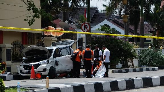 Indonesian policemen examine a car used by attackers outside the police headquarters in Pekanbaru, Riau, following attacks on May 16.