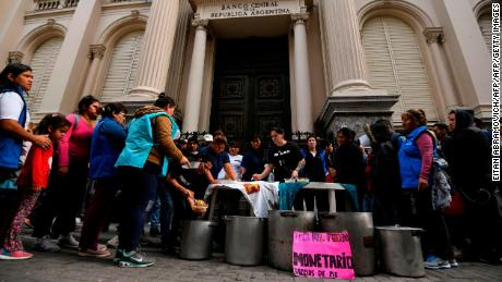 People receive meal from a soup kitchen outside Argentina's Central Bank in downtown Buenos Aires on May 15, 2018. - Argentina's currency faced a major test Tuesday as holders of peso-denominated securities readied for a potential $25 billion payout, squeezing government efforts to halt capital flight ahead of talks with the IMF. (Photo by EITAN ABRAMOVICH / AFP)        (Photo credit should read EITAN ABRAMOVICH/AFP/Getty Images)