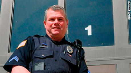 Dixon Police Officer Mark Dallas poses in front of Dixon High School in Illinois.
