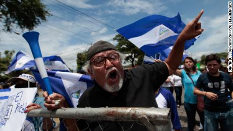 "An anti-government demonstrator shouts slogans in the surroundings of the Episcopal's Conference Seminary of Our Lady of Fatima, in Managua on May 16, 2018 while Nicaraguan President Daniel Ortega attends the so-called ""national dialogue"" talks with Nicaragua's Roman Catholic bishops and the opposition in a bid to quell a month of anti-government unrest that has seen more than 50 people killed. - The Church-mediated dialogue involved representatives from university students who are leading the protests against President Daniel Ortega as well as from business groups and unions. (Photo by DIANA ULLOA / AFP)        (Photo credit should read DIANA ULLOA/AFP/Getty Images)"