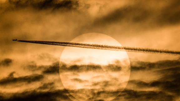 A plane flies in front of the sun. Chemicals that deplete the ozone layer, which protects us from the sun