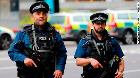 Armed police officers stand on duty following an incident in London in October.