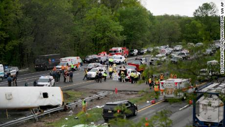 Emergency personnel work at the scene of a school bus and dump truck collision on Interstate 80 in Mount Olive Township, New Jersey.