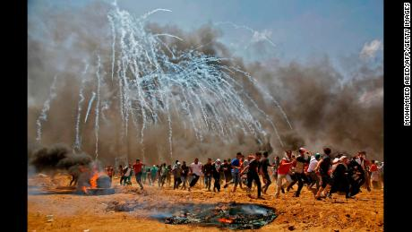 TOPSHOT - Palestinians run for cover from tear gas during clashes with Israeli security forces near the border between Israel and the Gaza Strip, east of Jabalia on May 14, 2018, as Palestinians protest over the inauguration of the US embassy following its controversial move to Jerusalem. (Photo by MOHAMMED ABED / AFP)        (Photo credit should read MOHAMMED ABED/AFP/Getty Images)