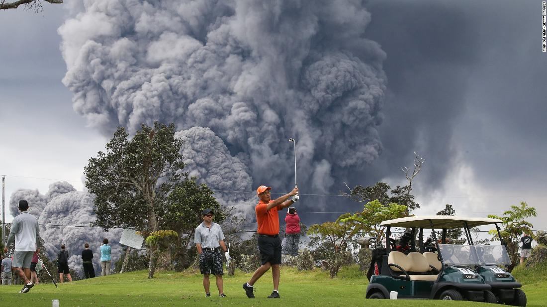 "People play golf on Hawaii's Big Island as an ash plume from the Kilauea volcano rises in the distance on Tuesday, May 15.  The volcano erupted earlier this month, sending a smoldering flow of lava into residential areas. <a href=""https://www.cnn.com/interactive/2018/05/us/hawaii-kilauea-volcano-eruption-cnnphotos/"" target=""_blank"">See more photos</a>"
