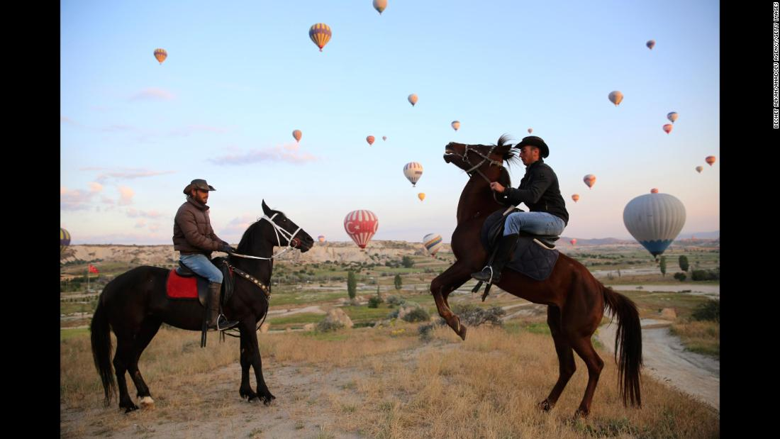 "Men ride horses as hot-air balloons fly in Turkey's Cappadocia region on Monday, May 14. Cappadocia is known as ""The Land of Beautiful Horses,"" and it is also famous for its ""fairy chimney"" rocks, hot-air balloon trips and underground cities."