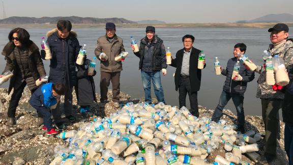 Activists in South Korea pose with bottled care packs for the North near the DMZ
