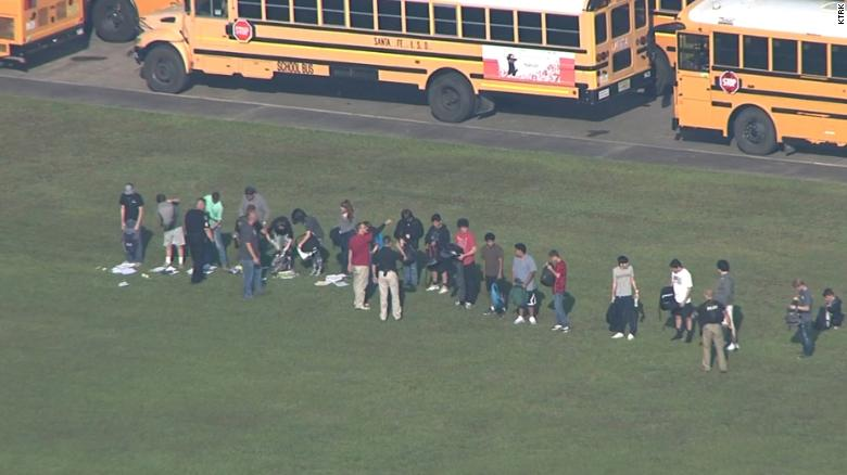 Students empty their backpacks outside Santa Fe High School Friday.