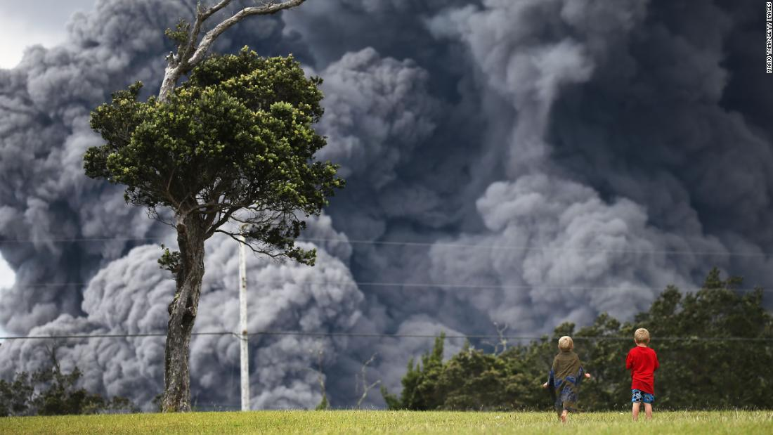 Boys watch at a golf course as an ash plume rises in the distance from the Kilauea volcano on Hawaii's Big Island on Tuesday.