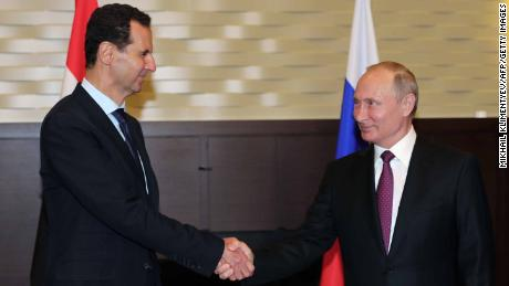 Russian President Vladimir Putin (R) shakes hands with his Syrian counterpart Bashar al-Assad during their meeting in Sochi on May 17, 2018. (Photo by Mikhail KLIMENTYEV / SPUTNIK / AFP)        (Photo credit should read MIKHAIL KLIMENTYEV/AFP/Getty Images)