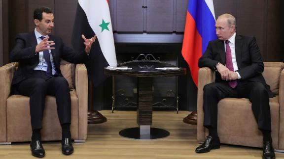 Russian President Vladimir Putin speaks with his Syrian counterpart Bashar al-Assad during their meeting in Sochi on May 17, 2018.