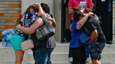 People embrace outside the Alamo Gym where students and parents wait to reunite following a shooting at Santa Fe High School Friday, May 18, 2018, in Santa Fe, Texas. ( Michael Ciaglo/Houston Chronicle via AP)