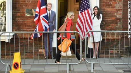TOPSHOT - A pedestrian walks past cut-out figures of Britain's Prince Harry and US actress Meghan Markle in Windsor on May 17, 2018, two days before the Royal wedding. - Britain's Prince Harry and US actress Meghan Markle will marry on May 19 at St George's Chapel in Windsor Castle. (Photo by Oli SCARFF / AFP)        (Photo credit should read OLI SCARFF/AFP/Getty Images)
