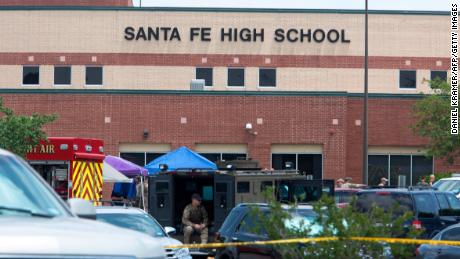 "Emergency crews gather in the parking lot of Santa Fe High School where at least ten people were killed on May 18, 2018 in Santa Fe, Texas. - At least ten people were killed when a student opened fire at his Texas high school on May 18, 2018, as President Donald Trump expressed ""heartbreak"" over the latest deadly school shooting in the United States. The shooting took place as classes were beginning for the day at Santa Fe High School in the city of the same name, located about 30 miles (50 kilometers) southeast of Houston.""There are multiple fatalities,"" Harris County Sheriff Ed Gonzalez told reporters. ""There could be anywhere between eight to 10, the majority being students."" (Photo by Daniel KRAMER / AFP)        (Photo credit should read DANIEL KRAMER/AFP/Getty Images)"