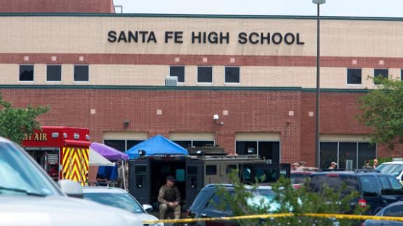 """Emergency crews gather in the parking lot of Santa Fe High School where at least ten people were killed on May 18, 2018 in Santa Fe, Texas. - At least ten people were killed when a student opened fire at his Texas high school on May 18, 2018, as President Donald Trump expressed """"heartbreak"""" over the latest deadly school shooting in the United States. The shooting took place as classes were beginning for the day at Santa Fe High School in the city of the same name, located about 30 miles (50 kilometers) southeast of Houston.""""There are multiple fatalities,"""" Harris County Sheriff Ed Gonzalez told reporters. """"There could be anywhere between eight to 10, the majority being students."""" (Photo by Daniel KRAMER / AFP)        (Photo credit should read DANIEL KRAMER/AFP/Getty Images)"""