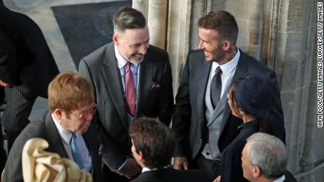 WINDSOR, UNITED KINGDOM - MAY 19:  David and Victoria Beckham (both right) talk with Sir Elton John (L) and David Furnish (C) as they arrive in St George's Chapel at Windsor Castle for the wedding of Prince Harry to Meghan Markle on May 19, 2018 in Windsor, England.. (Photo by Danny Lawson - WPA Pool/Getty Images)