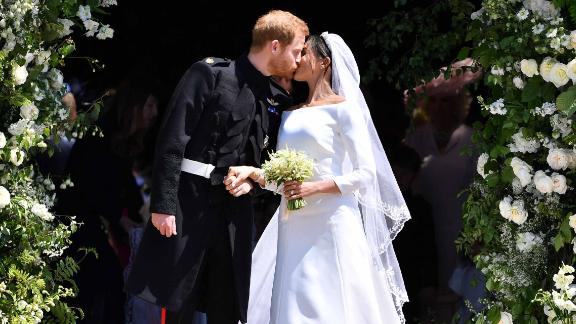 Harry and Meghan kiss outside the West Door.
