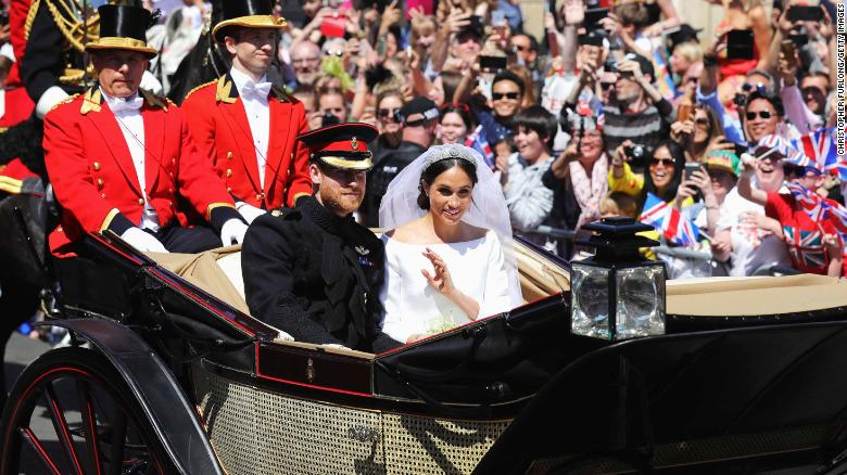 Prince Harry and Meghan wave during their carriage procession.