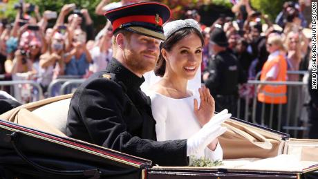 Harry and Meghan ride in an open carriage.