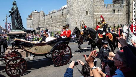 WINDSOR, ENGLAND - MAY 19: Prince Harry, Duke of Sussex and the Duchess of Sussex ride in the Ascot Landau carriage during the procession after getting married at St George's Chapel, Windsor Castle on May 19, 2018 in Windsor, England. Prince Henry Charles Albert David of Wales marries Ms. Meghan Markle in a service at St George's Chapel inside the grounds of Windsor Castle. Among the guests were 2200 members of the public, the royal family and Ms. Markle's Mother Doria Ragland. (Photo by Jack Taylor/Getty Images)