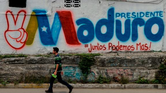 A man walks past a graffiti in support of Venezuelan President Nicolas Maduro, in Barquisimeto, Venezuela, on May 19, 2018 on the eve of the country