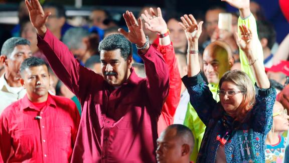 Venezuela's President Nicolas Maduro and his wife, Cilia Flores, wave to supporters at the presidential palace in Caracas.