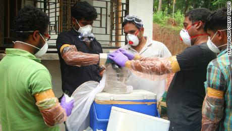 Animal Husbandry department and Forest officials deposit a bat into a container after catching it inside a well at Changaroth in Kozhikode in the Indian state of Kerala on May 21, 2018. - A deadly virus carried mainly by fruit bats has killed at least three people in southern India, sparking a statewide health alert May 21. Eight other deaths in the state of Kerala are being investigated for possible links to the Nipah virus, which has a 70 percent mortality rate. (Photo by - / AFP)        (Photo credit should read -/AFP/Getty Images)