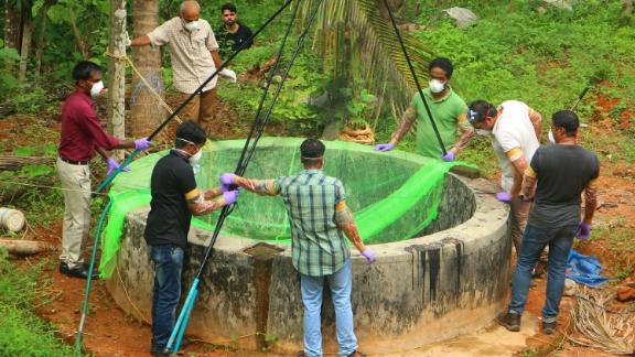 Officials inspect a well to catch bats in Kozhikode district in India's Kerala state after the outbreak.
