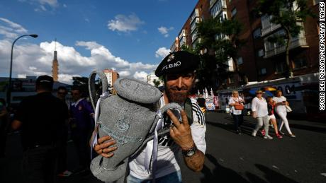 A Real Madrid football team fan holds a replica of the Champions League trophy in the surroundings of the Santiago Bernabeu stadium in Madrid on June 3, 2017 during the UEFA Champions League football match final Juventus vs Real Madrid CF held at the National Stadium of Wales in Cardiff. / AFP PHOTO / OSCAR DEL POZO        (Photo credit should read OSCAR DEL POZO/AFP/Getty Images)