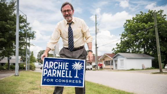 Democratic congressional candidate Archie Parnell places a campaign sign in the grass June 19, 2017 in Bishopville, South Carolina.