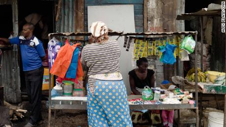 Women sell bananas, baby diapers, and other items on a street in Kibera, Africa's biggest slum.