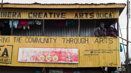 Two men stand chatting on the balcony of a community arts center in the heart Kibera.