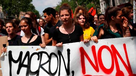 "Demonstrators carry a banner reading ""Macron No"" during a strike in Paris."