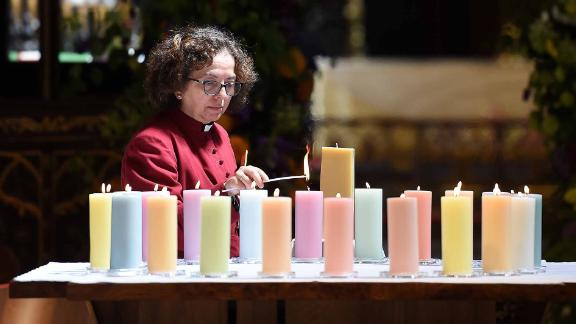 A member of the clergy lights candles for the victims of Mancester Arena attack.