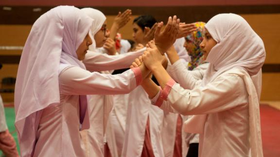 Schoolgirls practise a self-defence move to ward off an attacker if approached from the front in New Delhi, India.