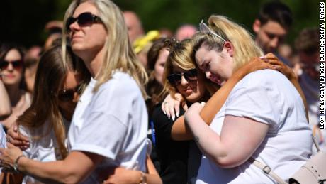 MANCHESTER, ENGLAND - MAY 22:  People hug as they observe one minute silence as they watch the outside broadcast of The Manchester Arena National Service of Commemoration at Manchester Cathedral on May 22, 2018 in Manchester, England. Twenty-two people were killed and hundreds injured when Salman Abedi detonated a bomb at the end of an Ariana Grande concert at Manchester Arena on 22 May 2017.  (Photo by Leon Neal/Getty Images)
