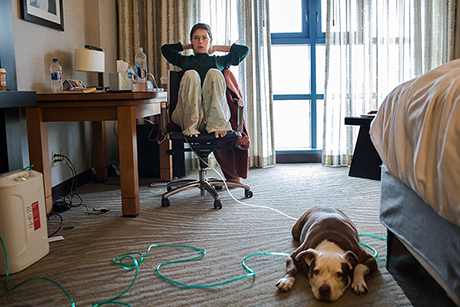 Claire Wineland sits in her hotel room with dog Daisy before heading to evaluations at the Center for Transplantation at UC San Diego Health.