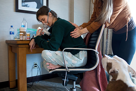Claire breathes in medicine through a nebulizer as Larissa pounds her back with cupped hands to help loosen mucus in her airways.