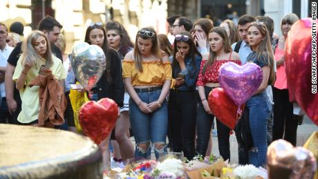 People pay their respects as they look at tributes left in central Manchester on May 22, 2018, the one-year anniversary of the  Manchester Arena attack.
