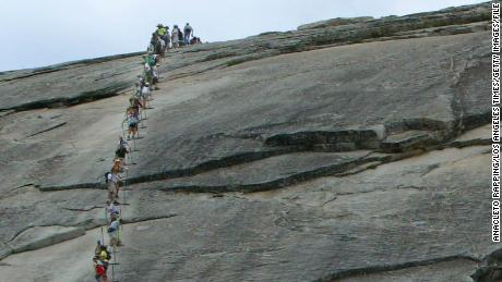 The trail to Half Dome in Yosemite National Park is the busiest and most popular trail in the park. Due to trail repair work hikers and climbers are prohibited on the last 1/2 mile of the trail to the summit of Half Dome from 7:00am? 4:00pm Monday through Thursday. During the first weekend of the trail closure ( 7/13/02), which will run thru September 19, hikers by the hundreds took advantage of the open trail. Hikers ascend and descend the cables on Half Dome.  (Photo by Anacleto Rapping/Los Angeles Times via Getty Images)