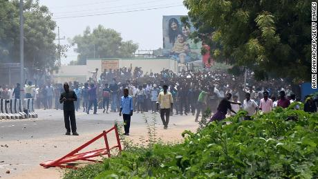 Indian protestors throw stones towards police officials in the southern Indian city of Tuticorin some 600 kilometres (375 miles) south of Chennai on May 22, 2018, during a protest rally held to demand the closure of a copper factory due to pollution concerns. - Indian police have killed 12 demonstrators after opening fire on thousands of people demanding the closure of a copper factory due to pollution concerns, a police officer said. Protesters rampaged for hours in the southern state of Tamil Nadu calling for the closure of the plant owned by British-based mining giant Vedanta Resources. (Photo by ARUN SANKAR / AFP)        (Photo credit should read ARUN SANKAR/AFP/Getty Images)