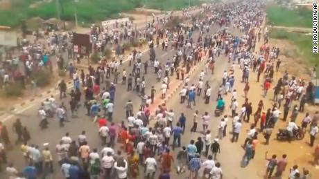 This frame grab from video provided by KK Productions shows protestors crowd a road in Tuticorin, in the southern Indian state of Tamil Nadu, Tuesday, May 22, 2018. Police opened fire Tuesday on protesters demanding the closure of a south Indian copper plant, killing nine people, officials said. The violence came amid months of protests against the Sterlite copper smelting plant in the town of Tuticorin, which demonstrators say has polluted the area's groundwater and put local fisheries at risk. (KK Production via AP)